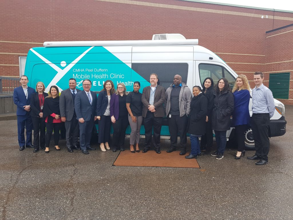 CMHA Team standing infront of the Mobile Health Clinic powered by TELUS